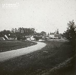 B025 Chemin de terre menant à un village