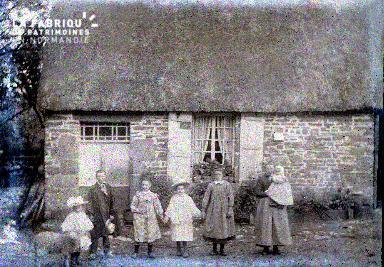 Groupe d'enfants devant une maison à toit de chaume