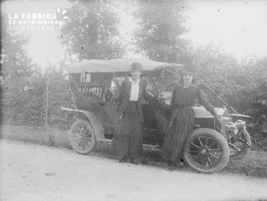 Femmes portant un chapeau posant devant une voiture