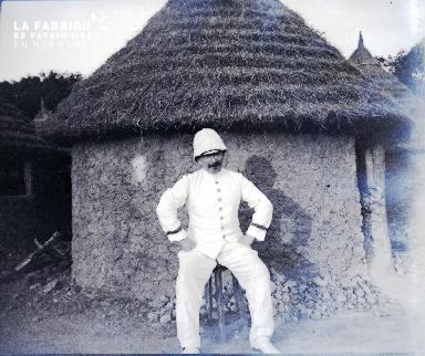 Afrique-Colon assis devant une hutte