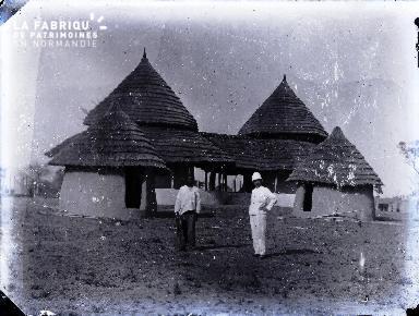 Afrique-Colon et Africain devant un batiment