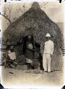 Afrique-Colon et famille africaine devant une hutte