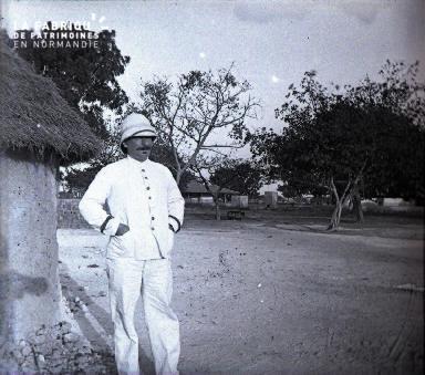 Afrique - Colon posant devant une hutte africaine