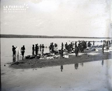 Afrique-Hommes et femmes lavant leur linge au bord de l'eau