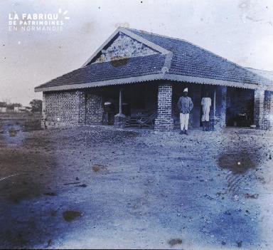 Afrique-Hommes sous le préau d'un batiment en brique