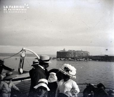 Bateau et ses passagers, derrière un fort en bout de jetée