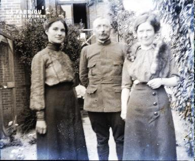 Deux femmes un homme dans l'allée d'un jardin