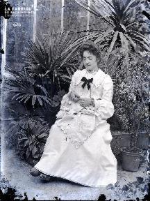 Jeune femme brodant devant la serre