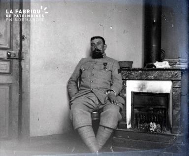 Militaire décoré assis près d'un poêle