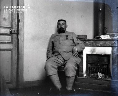 Militaire assis près d'un poële