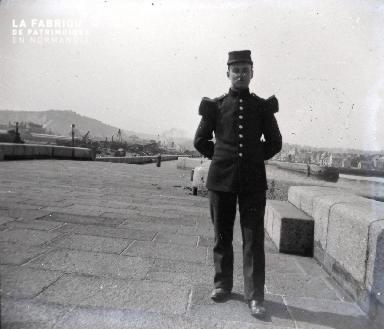 Un militaire prend la pose près d'un port