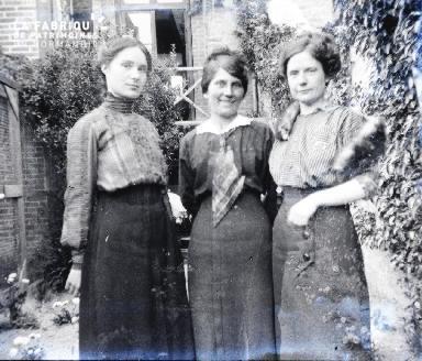 Trois femmes dans l'allée d'un jardin