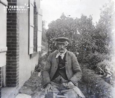Un vieil homme devant sa maison