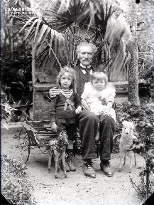Vieil homme et ses deux petites filles devant la serre
