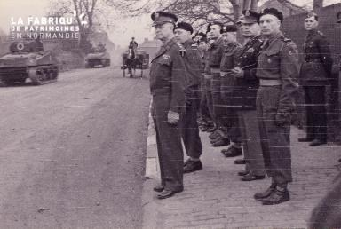Groupe de militaires regardant passer les chars dans la rue