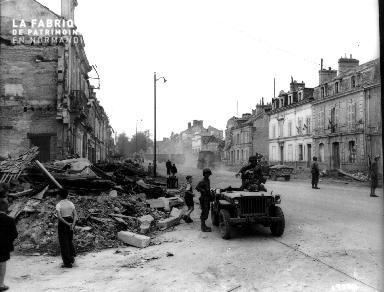 Scène de rue à Alençon (civils, soldats et jeeps)