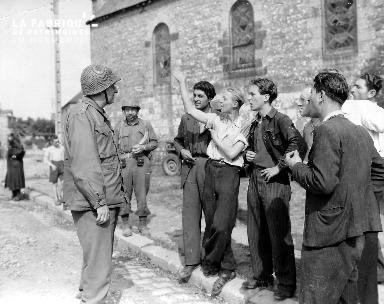 Jeunes hommes saluant un soldat américain
