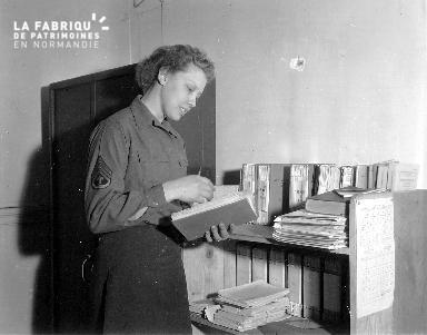 Femme Wac (women's army corps) lisant des documents