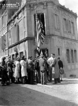 Attroupement devant le drapeau américain à Trevières