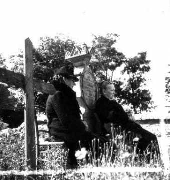 Femmes assises dans le cimetière à Saint Ouen de Rots
