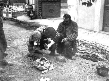 Soldat infirmier canadien portant secours à un prisonnier allemand
