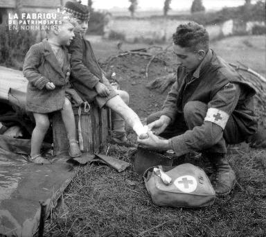 Deux enfants soignés par un soldat américain (croix rouge)