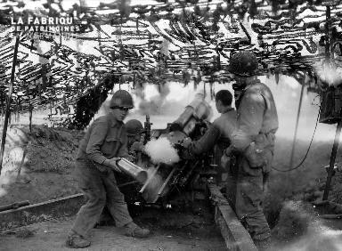 Soldats américains autour d'un obusier sous une tente de camouflage