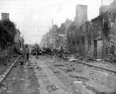 Progression de soldats américains dans les ruines de Juvigny le Tertre