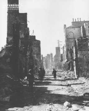 Soldats progressant parmi les ruines de Mortain