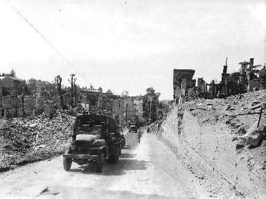 Camionnettes traversant une ville dévastée par les bombardements en 1944