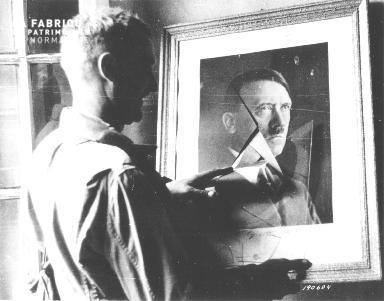 Soldat regardant le portrait brisé d'Adolf Hitler