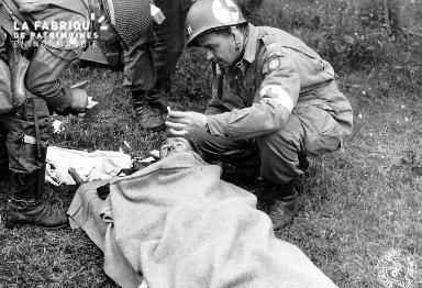 Un capitaine médecin donne une cigarette à une blessé sur une civière
