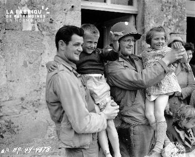 Soldats américains tenant dans leurs bras des enfants normands