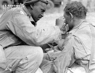 Soldat noir américain soigne un soldat blanc