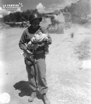 Soldat américain portant un bébé et une caméra