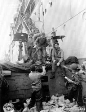 Dans le secteur d'Utah Beach, des femmes (WAC : women's Army Corps) descendent prudemment d'un paquebot par un escalier.