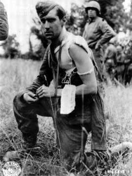 """Prisonnier allemand blessé portant une étiquette mentionnant : """"Prisonner of War""""."""