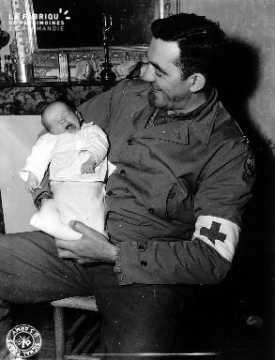 Un bébé baille dans les bras de l'officier Keseric Nicholas E. (Major)