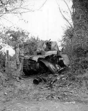 Un sergent américain armé devant une épave d'un char de combat allemand (panzer)