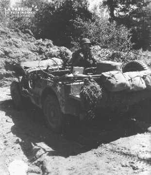 A bord d'une jeep, le private James E. Lough de Moundsville au téléphone