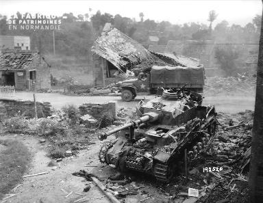 Épave d'un char de combat allemand (panzer) au milieu des décombres à Pont Farcy.
