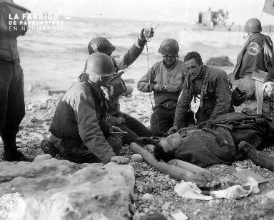 Soldats américains effectuant une transfusion à un blessé