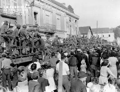 Prisonniers allemands à bord de camions, surveillés par des soldats américains sous les yeux des villageois de Châteauneuf sur Sarthe.