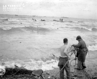 A l'aide dune corde, deux soldats essaient d'aider les naufragés (secteur Omaha)