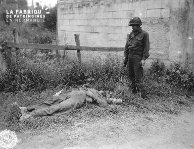 Soldat américain fixant un cadavre d'un soldat allemand