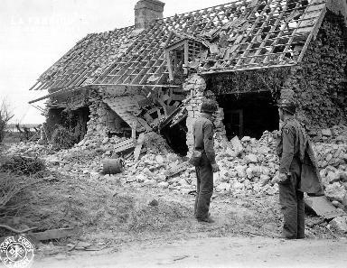 Parachutistes devant une maison détruite
