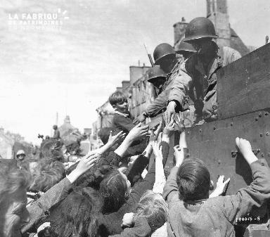 Petit garçon dans un char américiain et distribution de bonbons
