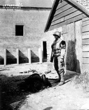 Policier militaire américain prés d'un corps de soldat allemand au sol