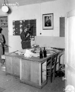 Policier militaire fixant le portrait d'Adolf Hitler à Saint-Clair-Sur-Elle