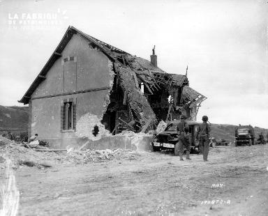 Soldats américains devant une maison détruite par les bombardements à Saint-Laurent-sur-Mer (secteur Omaha)